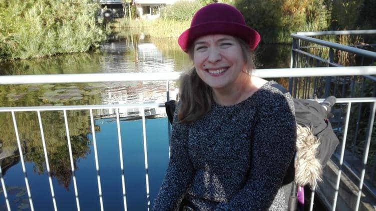 Hier ist ein schönes Bild von mir auf der Veranstaltung von Vibra. Im Hintergrund ist ein Teich. Ich habe einen grauen Pulli an und ein breites Lächeln auf dem Gesicht. Meinen Kopf verziert ein roter Melonenhut. Und ich habe noch einen seitlichen Zopf. Und es scheint die Sonne.
