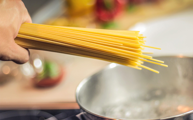 Ein Bündel Spaghetti wird in einen Topf gelegt.
