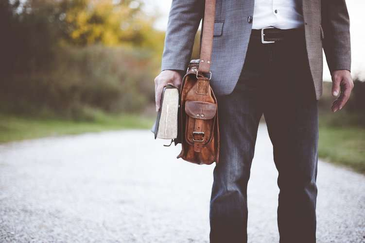 Unterkörper eines Mannes mit Ledertasche und Buch in der Hand