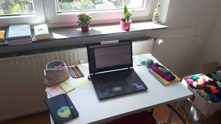 Schreibtisch mit Laptop, Stiften und Karteikarten