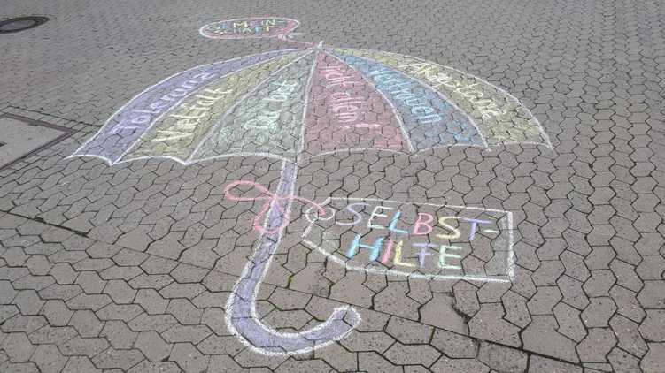Kreidebild eines Regenschirms. Auf dem Schirm stehen die Worte: Toleranz, Vielfalt, Akzeptanz, Vertrauen und Du bist nicht allein.