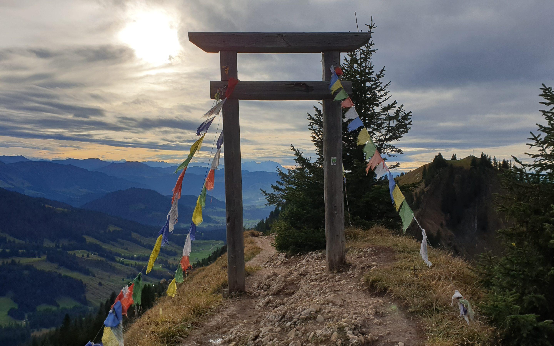 Durchgang auf einem Gipfel, im Hintergrund blitzt die Sonne zwischen den Wolken hervor