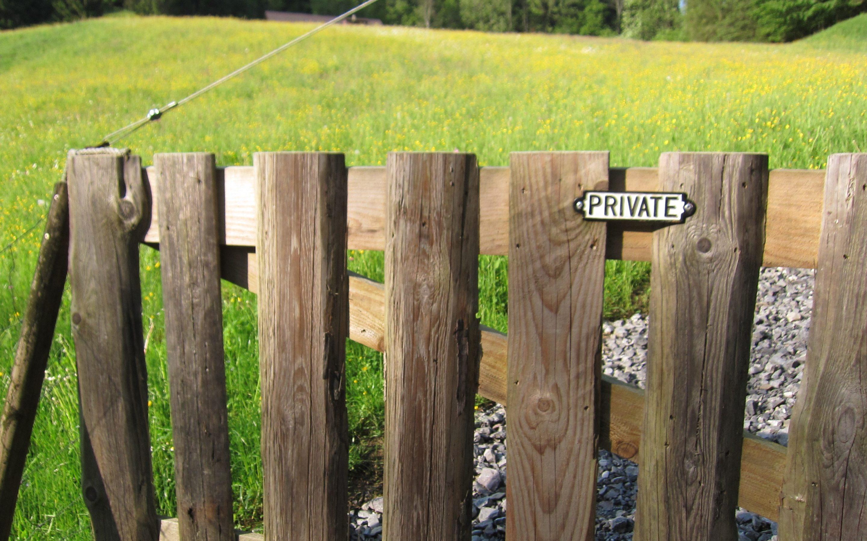 """Zaun, auf dem """"private"""" steht, im Hintergrund Natur (Wiese und Wald)"""