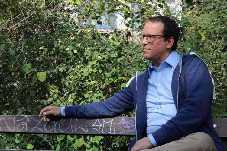 Foto des Autors auf einer Bank sitzend