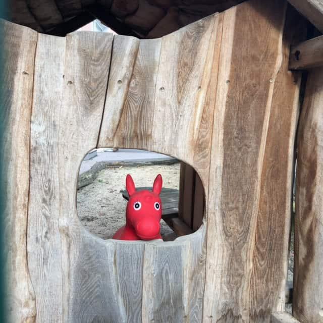 Rotes, treudoof guckendes Gummipferd auf Spielplatz