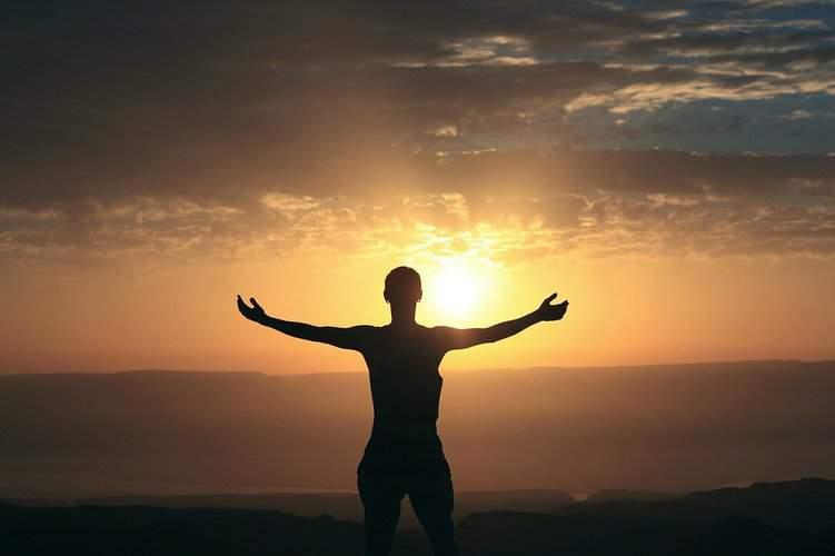 Person, die dem Sonnenuntergang mit weit geöffneten Armen entgegenblickt